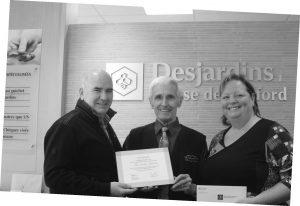M. Claude Frenière, directeur de la caisse de Bedford, remettant le certificat honorifique à M. Paul-André Choinière ainsi que le chèque à Marie Josée Proteau du Centre d'Action Bénévole de Bedford.