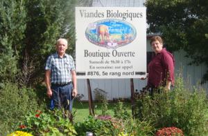 Richard et Isabelle devant l'étable et l'affiche annonçant les produits de la ferme.